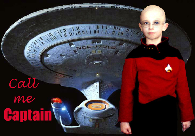 A child sized Captain Picard poses in front of the TNG Starship Enterprise