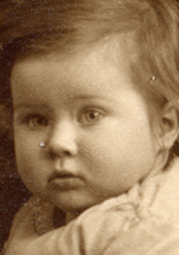 A close-up of baby's face shows the type of damage likely to be found on a print of this vintage.