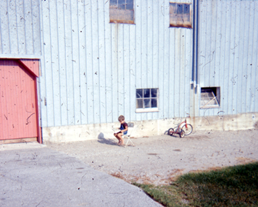 A little boy sits on a little chair in front of a metal barn reading in the sun.