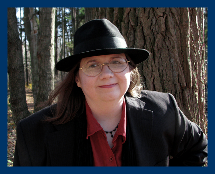 author photo wearing a black fedora & suit jacket over a red blouse in the autumn woods
