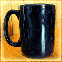 A deep blue coffee mug rests on a on wood table
