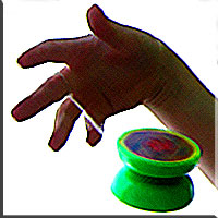 The green yoyo begins its descent from the hand above.